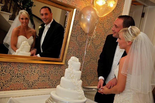 Wedding couple cutting the cake in the Mansion House