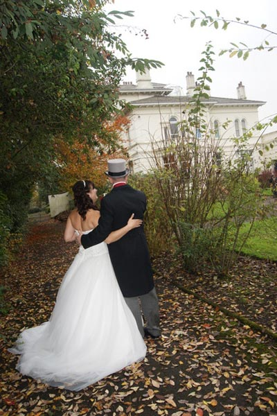 Wedding couple with their arms around each other whilst walking around the Mansion House gardens