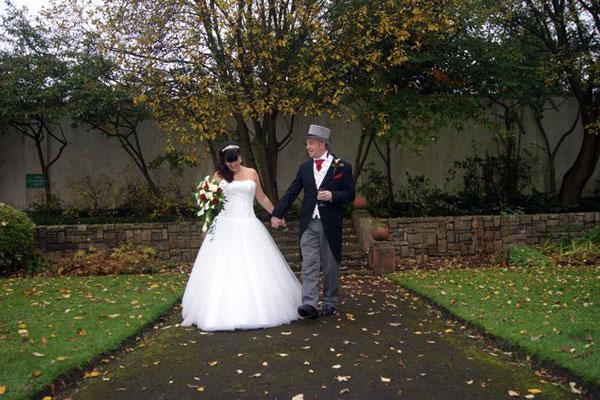 Wedding coupling walking around the Mansion House garden hand in hand