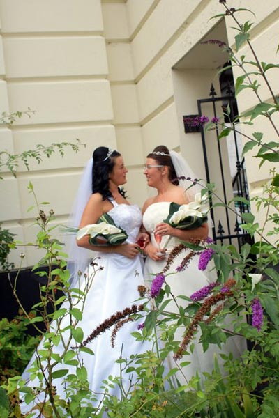 Wedding couple in front of the Mansion House with flowers in the foreground