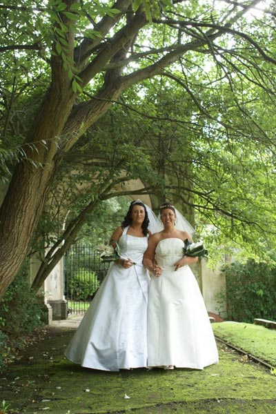Wedding couple walking under the trees of the Mansion House walled gardens