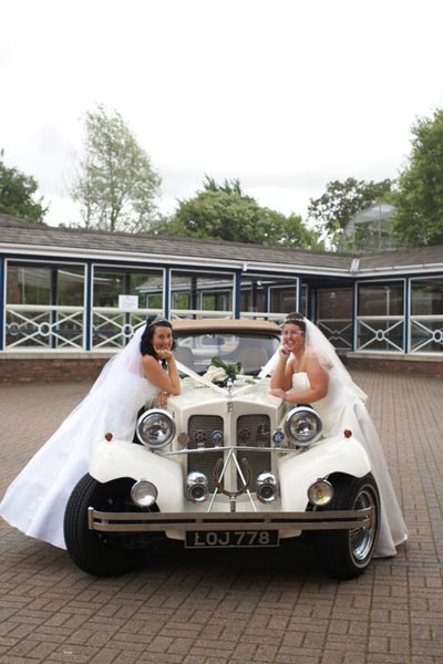 Wedding couple leaning on an antique car in the Mansion House courtyard