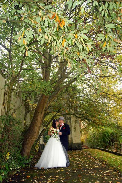 Wedding couple under the trees of the Mansion House garden