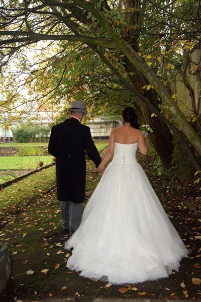 Wedding couple holding hands whilst walking around the Mansion House gardens