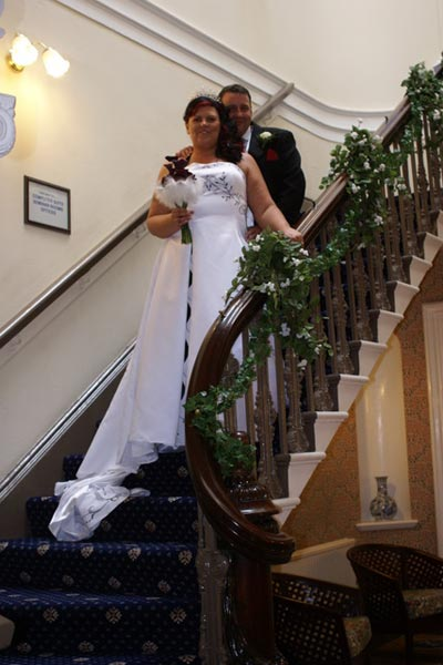 Wedding couple on the decorated hallway stairs of the Mansion House